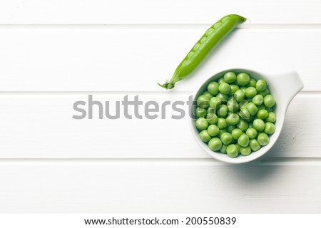 green peas in bowl on white wooden table - stock photo