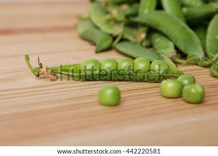 green peas in pods freshly picked on wood. Some green peas. Fresh green peas. green pods with peas as background. Green peas into a bowl. green peas in pods freshly picked on wooden background texture - stock photo