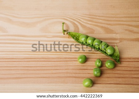 green peas in pods freshly picked on wood. Some green peas. Fresh green peas. green pods with peas as background. Green peas into a bowl - stock photo