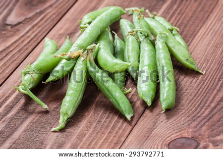 Green peas on old wooden background. - stock photo
