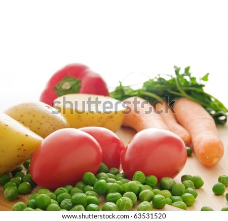 Green peas,tomatoes,potatoes,carrots,and a red pepper on a wooden plank - isolated on white background with copy space - stock photo