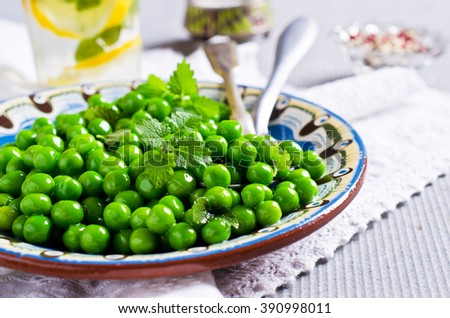 Green peas with mint in a bowl on a light background. Selective focus. - stock photo