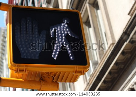 Green pedestrian signal with a little walking man indicating that it is safe to cross the intersection or crossroads - stock photo