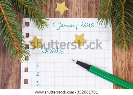 Green pen and notebook for writing resolutions and goals for new year, green christmas spruce branches - stock photo