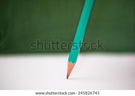 Green pencil on school board desk background. - stock photo
