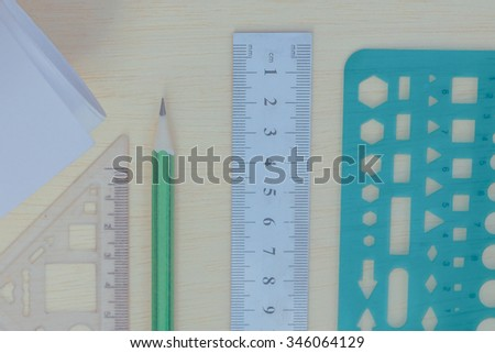 green pencil, steel ruler, triangle ruler and Geometry ruler on wood texture in vintage style