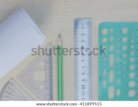 green pencil, steel ruler, triangle ruler, Geometry ruler and scroll on wood texture in vintage style