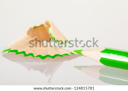 Green pencil with shavings on neutral background