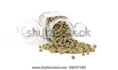 Green peppercorns spilling out of its spice jar, isolated on a white background. - stock photo