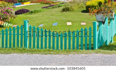 Green picket fence with road, green garden and flower