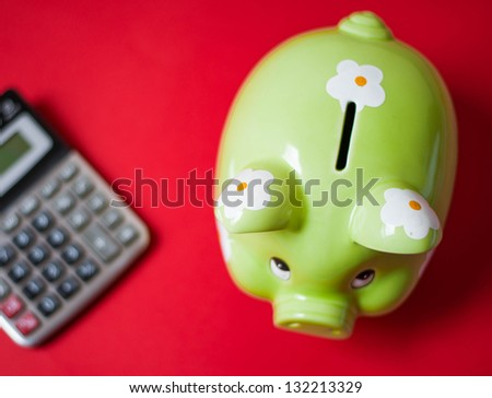 Green piggy bank and calculator on a red background - stock photo