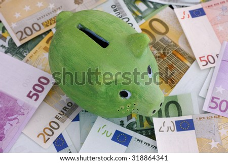 Green piggy bank and euro banknotes. Close up.