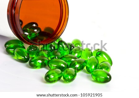Green pills and pill bottle on white background - stock photo