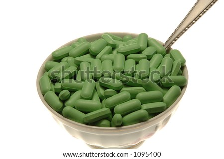 Green Pills in bowl with spoon