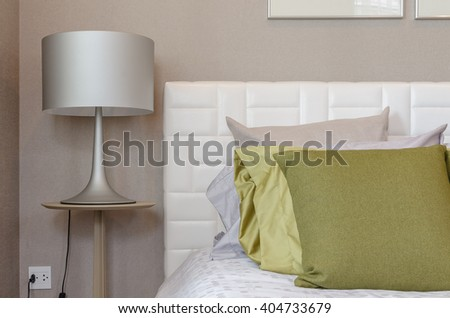 green pillw on bed with modern lamp style on wooden table side in bedroom