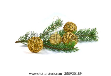 Green pine branch decorated with four balls of Christmas tree decorations. Three balls made of straw and a one glass bowl decorated with shiny gold sequins.Isolated on white. - stock photo