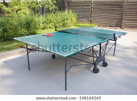 Green ping-pong table and rackets outdoors - stock photo