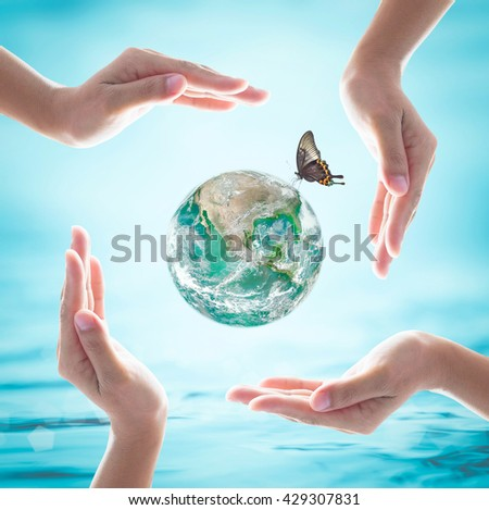 Green planet among women hands on turquoise blue water background: World ocean & environment protection day concept: Saving CSR BIO healthy earth planet: Element of the image furnished by NASA  - stock photo