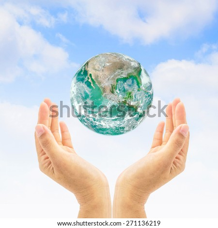Green planet over human hands on natural sky background : Saving environment and ozone layer concept  : Save the earth campaign : Pray for help and support : Elements of this image furnished by NASA  - stock photo