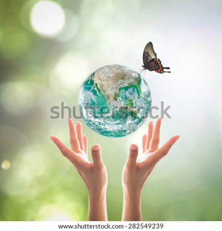 Green planet with butterfly over human hands  in blurred green bokeh background of natural tree leaves  facing sun flare : World environment day concept: Elements of this image furnished by NASA    - stock photo