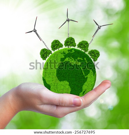 Green planet with trees and wind turbines in hand. - stock photo