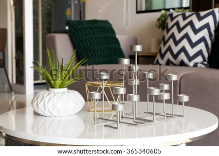 green plant in a vase and candle stand in living room - stock photo