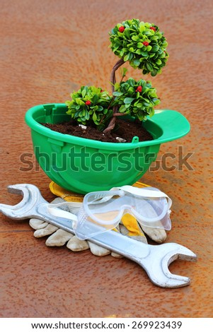 Green plant in green helmet on rusty background - environmental friendly industry concept - stock photo