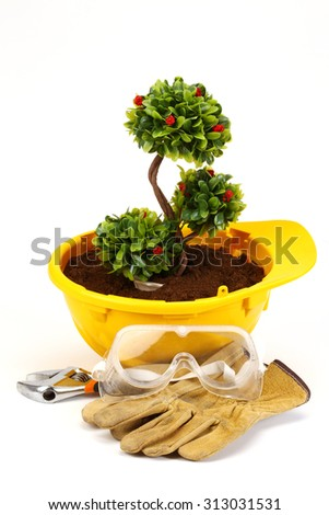 Green plant in  helmet on white - environmental friendly industry concept - stock photo