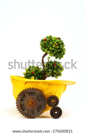 Green plant in yellow helmet and rusty gear on white - environmental friendly industry concept - stock photo