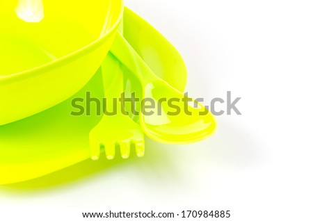 Green plastic bowl , fork , and spoon on isolated white background - stock photo