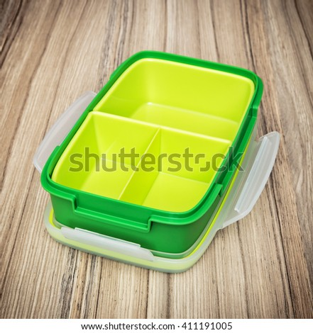 Green plastic box for food storage on the wooden background. Kitchen utensil. Close up photo. - stock photo