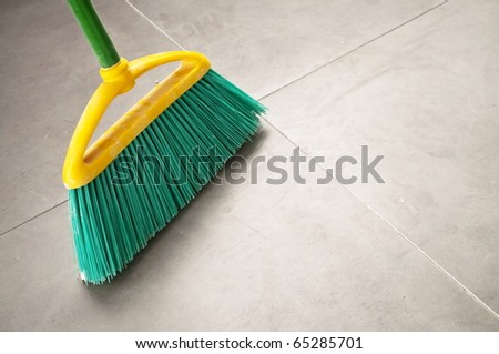Green plastic broom during a home cleaning