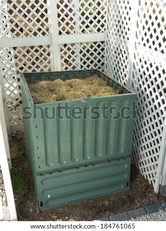 Green plastic compost bin full with lawn cut grass - stock photo