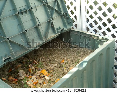 Green plastic compost bin full with lawn cut grass and domestic food scraps - stock photo