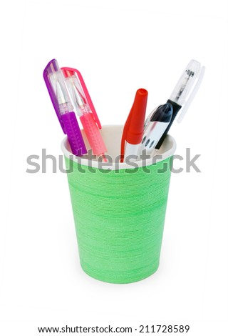 green plastic cup with pens on a white background isolated