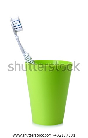 green plastic cup with toothbrush on white isolated background
