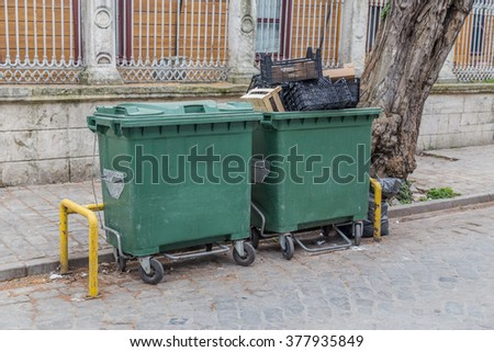 Green plastic garbage containers standing on a street with some garbage in them and nearby. - stock photo