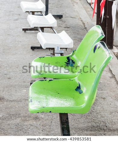 Green plastic seat near the platform of the rural station. - stock photo
