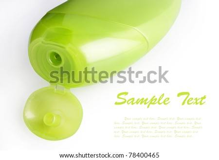 Green plastic shampoo bottle with an open lid isolated on white with sample text - stock photo