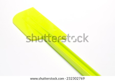 green plastic spatula on a white background