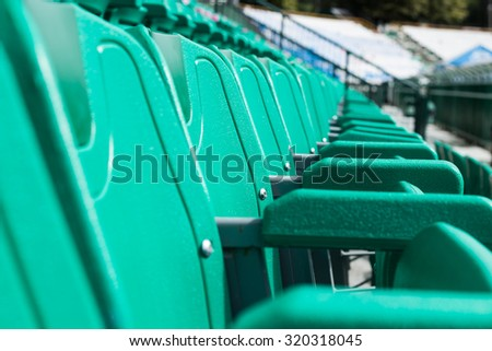 green plastic stadium seats in rows. The seats are filled the frame as background. , Empty Plastic Chairs at the Stadium - stock photo