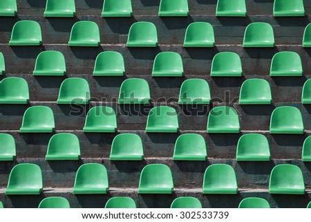 green plastic stadium seats in rows. The seats are filled the frame as background. This is a day shot of an empty stadium.     - stock photo