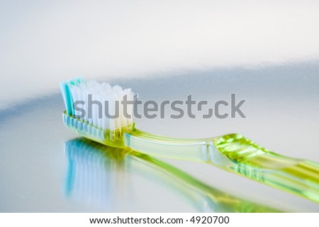 Green plastic toothbrush reflected on metallic surface. - stock photo