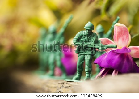 Green plastic toy soldier army unit running on top of an old weathered railway sleeper. Selective focus and wooden textured background and purple flowers - stock photo