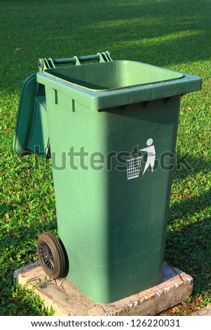 Green plastic trash recycling container in the park - stock photo