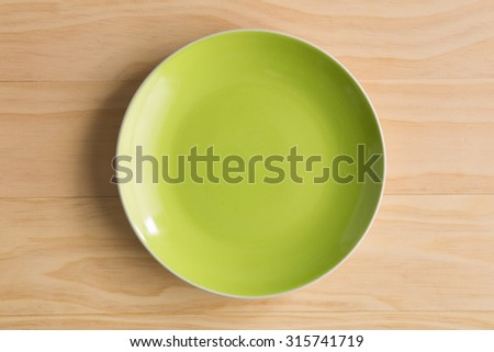 green plate on wooden background - stock photo