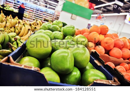 green pomelos in boxes in supermarket