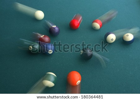 Green pool table with balls in motion - stock photo
