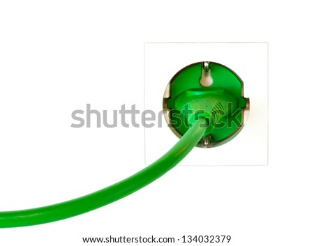 Green power plug in simple wall outlet against white background - stock photo