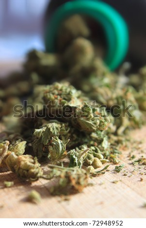 Green prescription cannabis spilling out of a bottle (shallow depth of field)